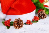 Leaves of mistletoe with Christmas hat on table on brick wall background