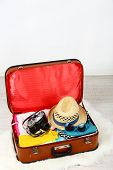 Female clothes and photo camera in old suitcase on light background