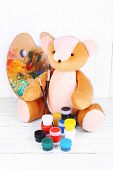 Toy bear, palette and paints on wooden wall background