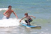 Father Teaching His Young Son How To Surf