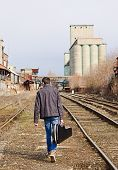 Young Man With Guitar Case In Hand Going Away By Rails. Rear View
