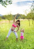 Pregnant mother with her daughter exercising