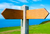 Blank Wooden Signpost With Two Arrows Over Clear Blue Sky With Copy Space