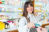 Pharmacist suggesting medical drug to buyer in pharmacy drugstore, customer pays by credit card