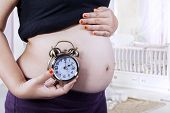 Pregnant Belly And Clock In Bedroom