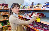 Borovichi, Russia - July 11, 2014: Young Woman Choosing Fresh Bakery Products At Shopping In Superma
