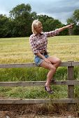 Mature Lady Sitting On A Fence