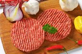 overhead view of raw minced beef burger with fresh onion, on the wooden cutting board