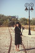 Retro Woman Wearing Coat And Hat Standing On Railroad