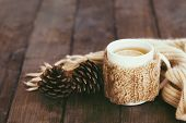 Cup of hot tea with lemon dressed in knitted warm winter scarf on brown wooden tabletop