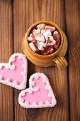 hot chocolat vintage mug, topping with marshmallow with heart cookies on textured wood