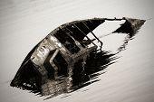 rusty sunken boat in ripples water