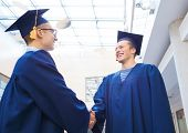 education, graduation and people concept - smiling students in mortarboards and gowns shaking hands outdoors