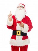 christmas, holidays, gesture and people concept - man in costume of santa claus with notepad pointing finger up