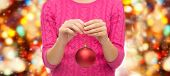 christmas, decoration, holidays and people concept - close up of woman in pink sweater holding christmas ball over red lights background