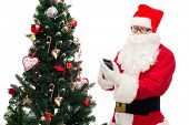 holidays, technology and people concept - man in costume of santa claus with smartphone and christmas tree