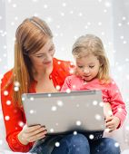 family, childhood, holidays, technology and people concept - happy mother and daughter with laptop computer at home