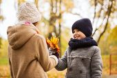 childhood, season and people concept - smiling little girl and boy with autumn leaves in park