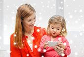 family, childhood, holidays, technology and people concept - happy mother and daughter with smartphone at home