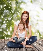 childhood, parenting and people concept - happy mother with little girl over wooden floor and green plants background