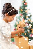 holidays, christmas, childhood and people concept - smiling little girl with gift box and teddy bear toy at home