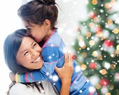 childhood, happiness, christmas, family and people concept - smiling little girl and mother hugging indoors