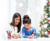 childhood, family, christmas and people concept - smiling little girl and mother or teacher drawing with coloring pencils indoors