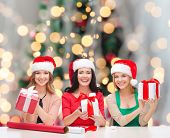 christmas, holidays, celebration, decoration and people concept - smiling women in santa helper hats with decorating paper and gift boxes over tree lights background