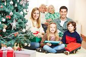 Family celebrating christmas with three generations under tree with gifts