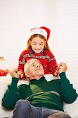 Happy girl and smiling grandfather playing together at christmas