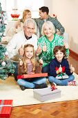 Happy family with grandparents making gift giving at christmas eve
