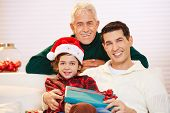 Happy child celebrating christmas with father and grandfather and gifts