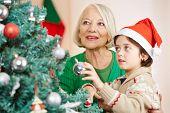 Boy and grandma hanging together christmas tree balls on a tree