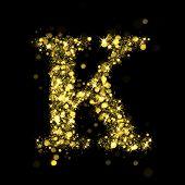 Sparkling Letter K on black background. Alphabet of golden glittering stars (glittering font concept). Christmas holiday illustration of bokeh shining stars character..