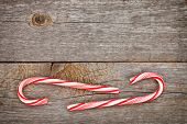 Two christmas candy cane over wooden background with copy space