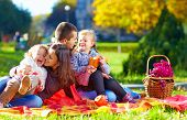 Happy Family On Autumn Picnic In Park