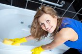 stock photo of window washing  - Smiling woman cleaning a bath with a sponge - JPG