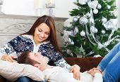 Young Happy Couple On The Sofa By Cristmas Tree