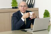 Mature Man in formalwear drinking coffee while sitting at his working place