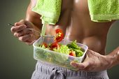 Close-up of a fitness man holding a bowl of fresh salad on black background