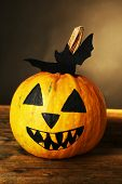 Halloween pumpkin on wooden table on dark color background