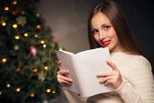 Woman in front of Christmas tree reading a book