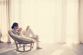 image of in front  - Young woman at home sitting on modern chair in front of window relaxing in her living room reading book and drinking coffee or tea - JPG