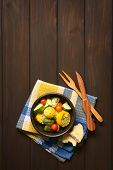 pic of sweet-corn  - Overhead shot of a bowl of baked vegetables of sweet corn zucchini cherry tomato with thyme toasted bread slice and wooden cutlery on the side photographed on dark wood with natural light - JPG