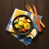 image of dark side  - Overhead shot of a bowl of baked vegetables of sweet corn zucchini cherry tomato with thyme toasted bread slice and wooden cutlery on the side photographed on dark wood with natural light - JPG