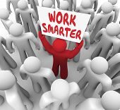 stock photo of productivity  - Work Smarter words on a sign held up by a worker or employee trying to improve or increase efficiency and productivity - JPG