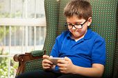 picture of indoor games  - Portrait of a cute little boy playing games on a smartphone at home