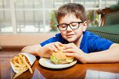image of junk food  - Little blond boy with glasses eating junk food at home - JPG