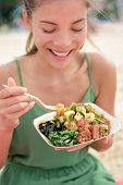 image of yellowfin tuna  - Woman eating local Hawaii food dish Poke bowl salad - JPG
