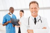 foto of maturity  - Cheerful mature doctor keeping arms crossed and smiling while his colleagues discussing x - JPG